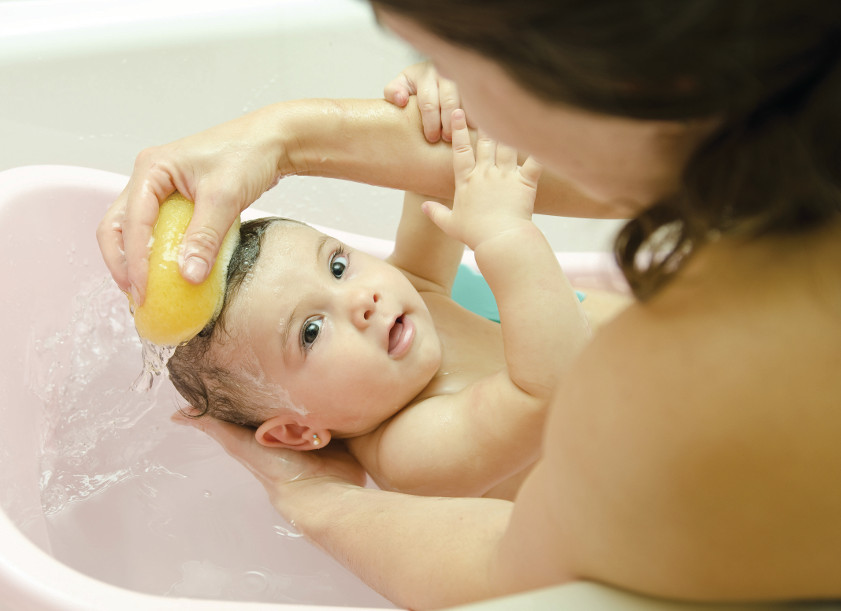 mother cleaning little baby in bathtub with sponge