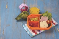 School lunch box for kids. Funny flower shaped sandwiches, fruits, vegetables and juice. Selective focus