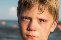 Crying boy's face close up. Shallow depth of field. Selective soft focus