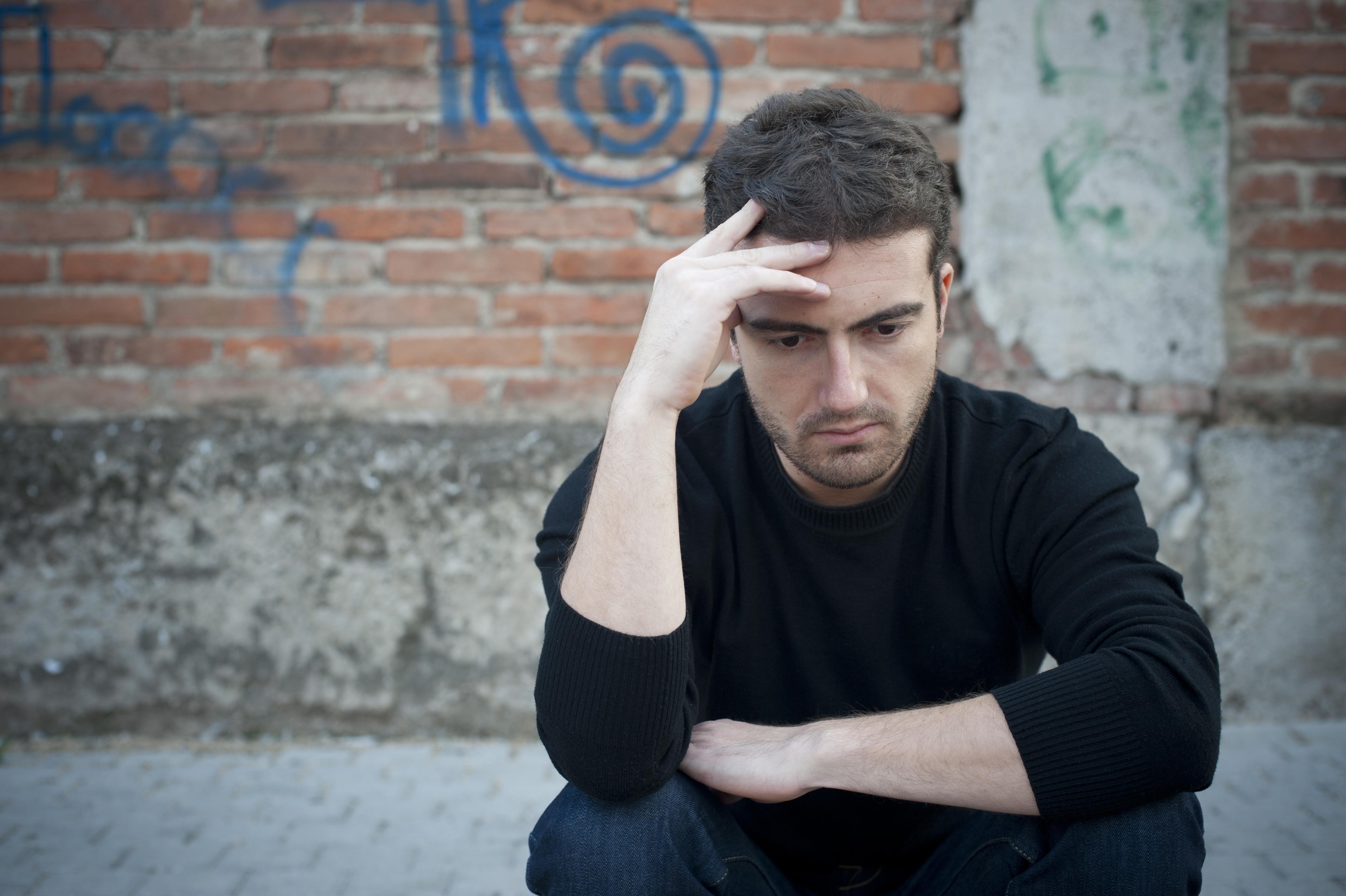 portrait of a sad man in a urban street
