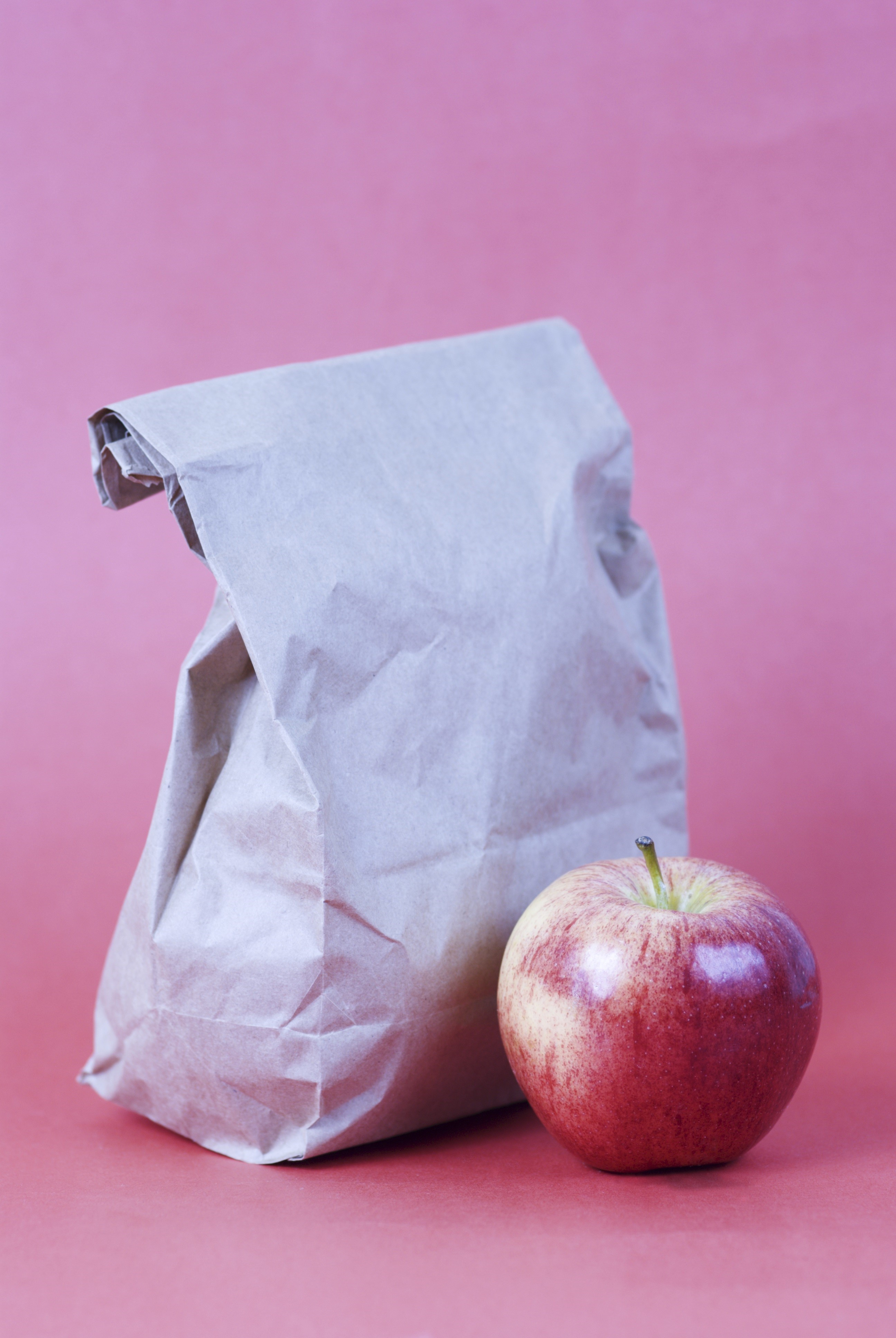 Brown bag lunch and apple with red background