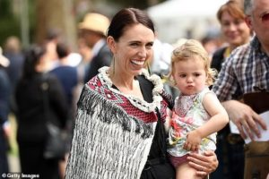 Jacinda holding Neve wearing traditional Maori dress