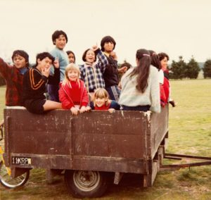 Jacinda as a young girl riding trailer with friends