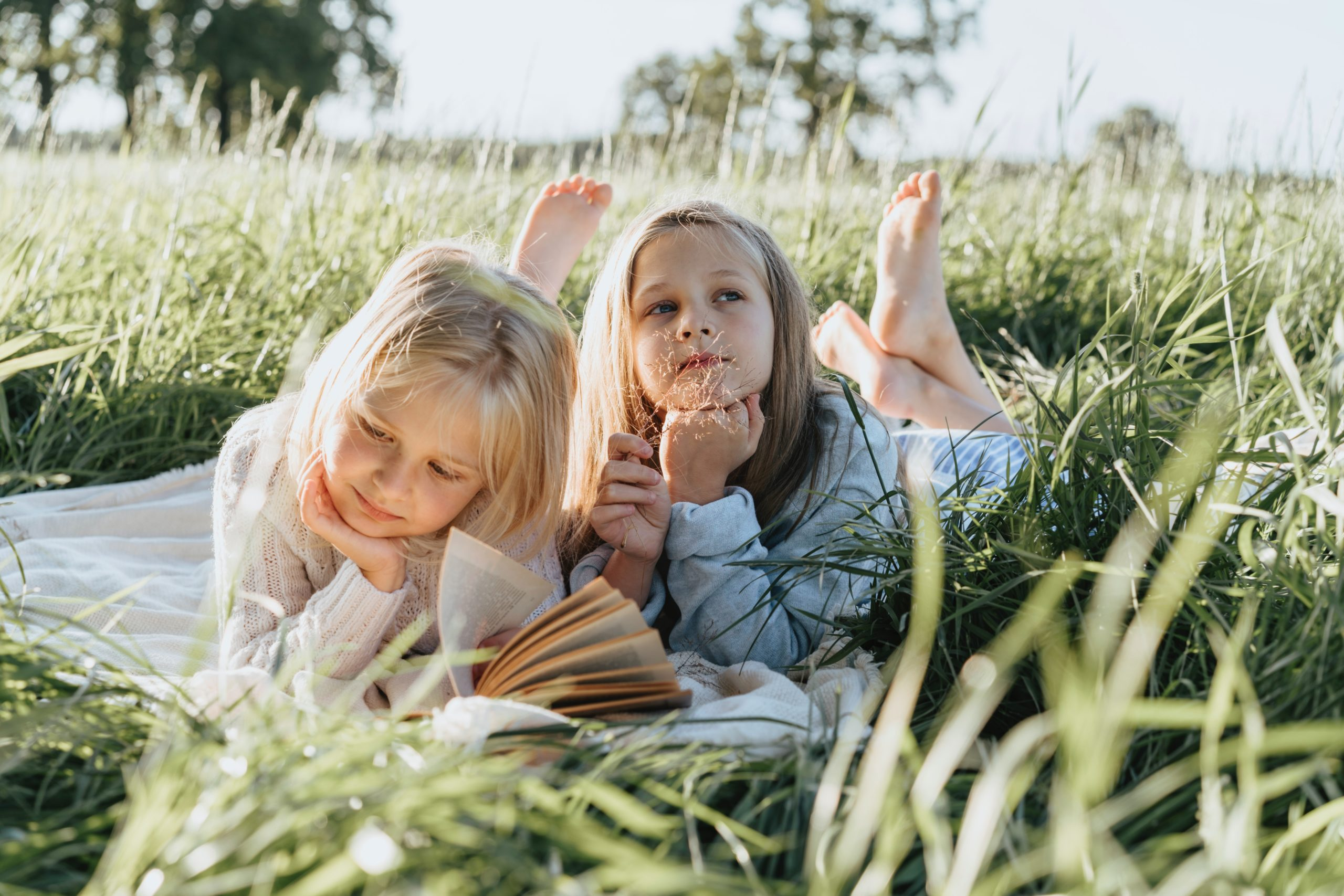 Two young sisters in grass