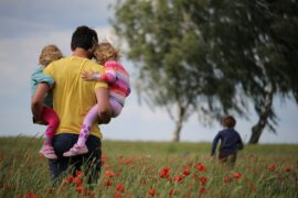 a father carries two of his children in a field