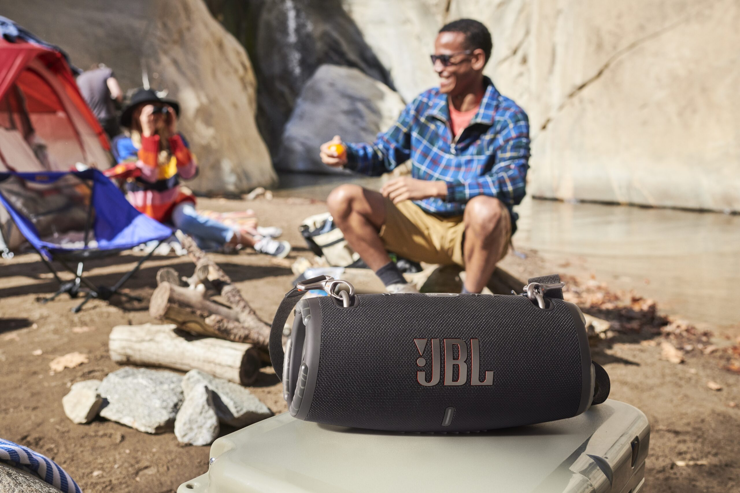 Man and woman at campground, JBL speaker in forgeround
