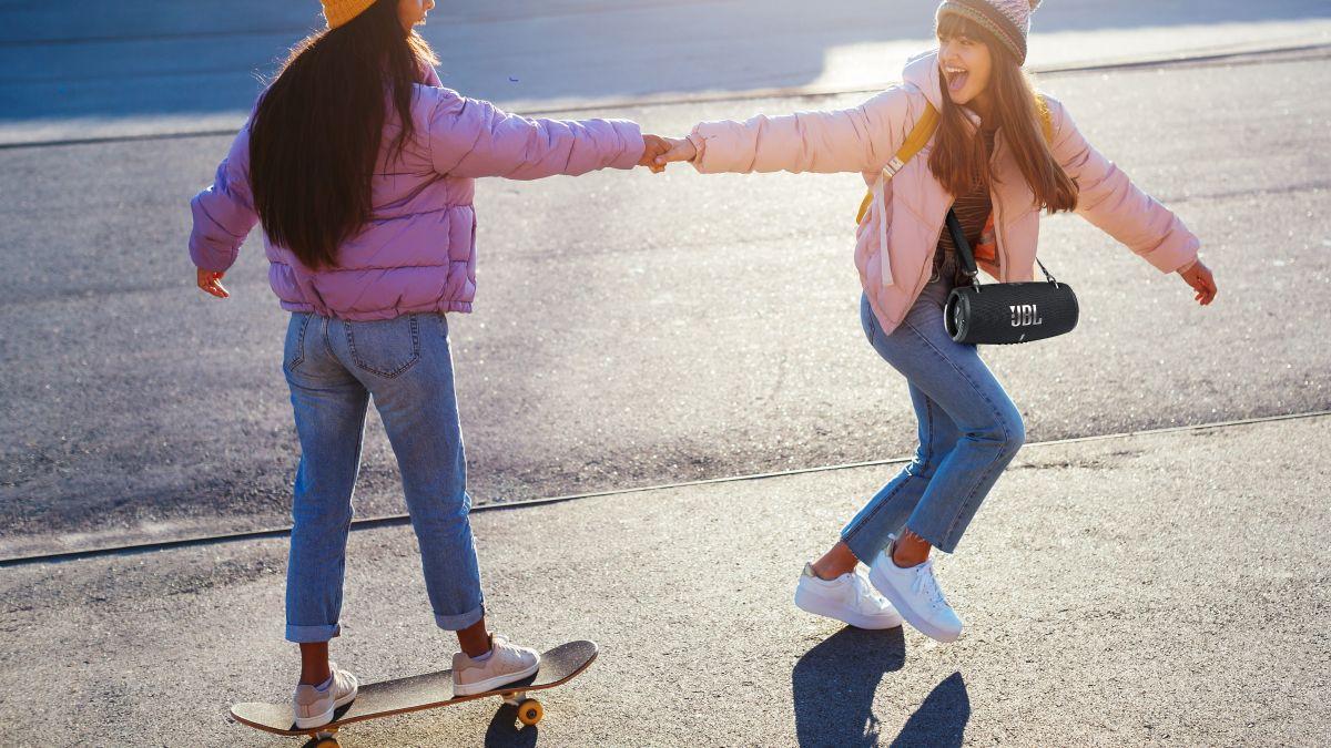 Girls holding hands skateboarding carrying speaker