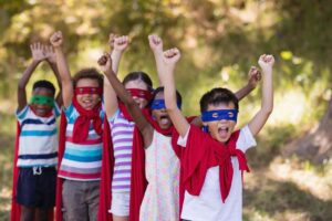 A group of children dressed up as super heroes in capes and masks
