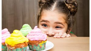 A little girl peers over the a countertop at a cupcake