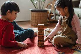 Two children sitting in the living room playing Jenga with wooden blocks