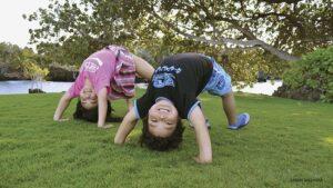 kids doing yoga outside on the grass